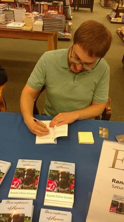 Literary Fiction author Randal Eldon Greene signs a copy of his debut novel, Descriptions of Heaven.